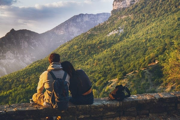 Lovers taking a rest and seating at the rock facing the mountain and enjoying the view