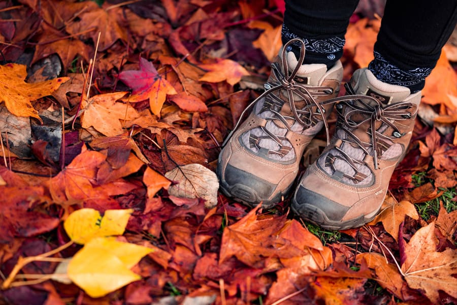 Hiking boots step on the red autumn leaves
